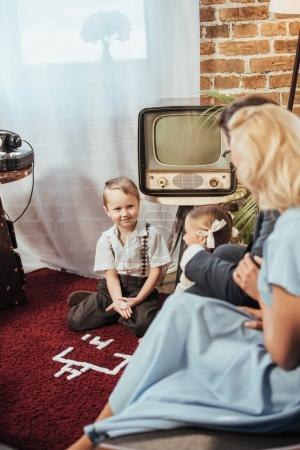 Photo for Selective focus of parents looking at adorable children playing at home, 50s style - Royalty Free Image