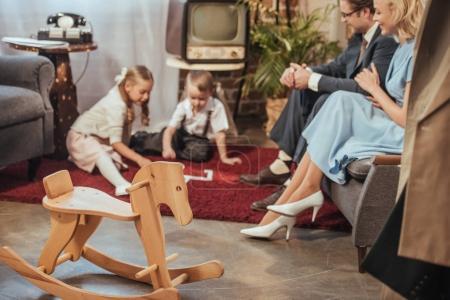 Photo pour Cheval à bascule en bois et heureuse années 50 style famille de passer du temps ensemble à la maison - image libre de droit