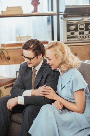 happy fifties style couple looking away while sitting on sofa and holding hands