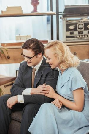 Photo for Happy fifties style couple looking away while sitting on sofa and holding hands - Royalty Free Image