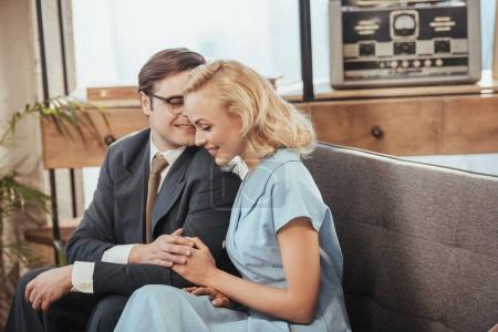 beautiful happy couple sitting on sofa and holding hands, 1950s style