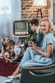 happy 50s style woman smiling at camera while sitting on sofa with husband and kids playing with domino tiles