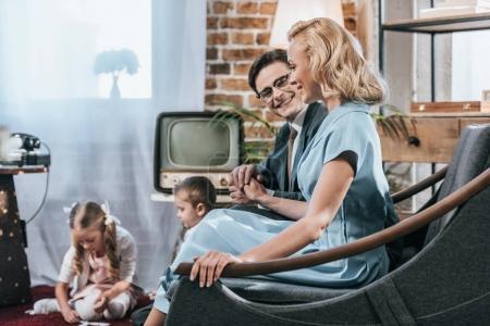 Photo pour Heureux parents de vieux assis sur le canapé et main dans la main tandis que des enfants jouant avec des carreaux de domino, style années 1950 - image libre de droit