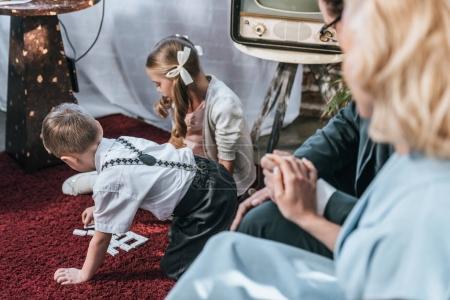 Photo pour Photo recadrée de parents assis sur le canapé et main dans la main tandis que des enfants jouant avec des carreaux de domino, style années 1950 - image libre de droit