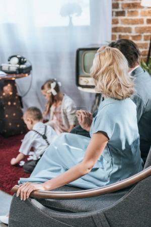 Photo for Parents sitting on sofa and holding hands while children playing with domino tiles, 1950s style - Royalty Free Image