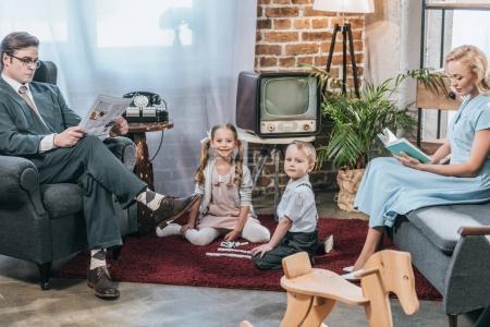 Foto de Padres leyendo el libro y el periódico mientras los niños juegan con dominó y sonriendo a cámara, estilo retro - Imagen libre de derechos