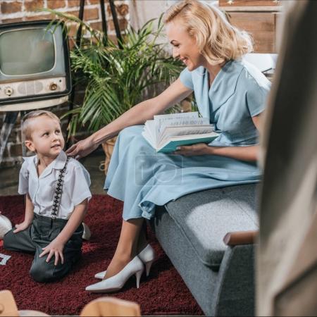 Photo pour Femme blonde heureuse lecture livre et en regardant mignon petit garçon jouant sur le tapis à la maison de famille de style années 1950 - image libre de droit