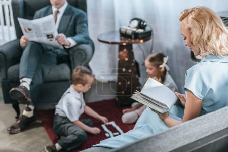 Photo pour Parents qui lisent le livre un journal tout en heureux enfants jouant avec des tuiles de domino, style années 1950 - image libre de droit