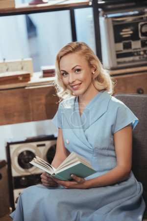 Photo for Beautiful blonde woman in blue dress holding book and smiling at camera, 50s style - Royalty Free Image