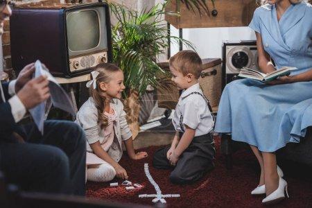 Foto de Reserva de tiro corto de padres leyendo un periódico mientras niños felices jugando con fichas de dominó, estilo vintage - Imagen libre de derechos
