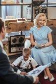 Adorable niño jugando en la alfombra mientras que padres leyendo el libro y periódico, familia de estilo de la década de 1950