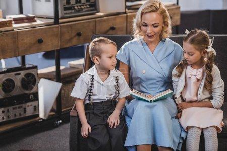 Photo pour Livre de lecture heureuse mère tout en restant assis avec d'adorables petits enfants sur canapé à la maison, famille de style années 50 - image libre de droit