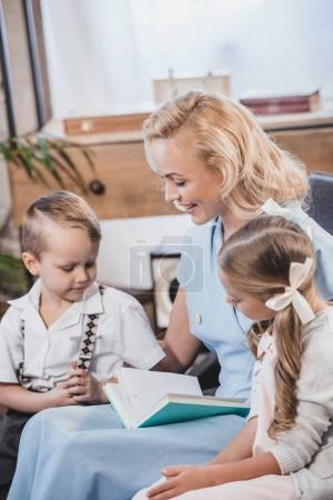 Photo for Happy mother with adorable little kids reading book together at home, 1950s style family - Royalty Free Image