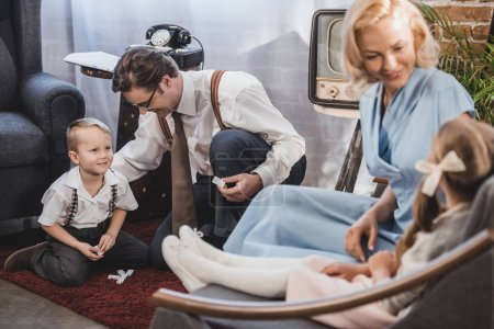 Photo for Happy mother and daughter sitting on sofa, while smiling father and son playing with domino tiles, 1950s style - Royalty Free Image