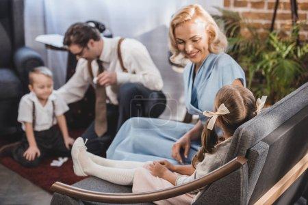 Photo pour Heureuse mère regardant mignonne petite fille assise sur le canapé pendant que père avec fils jouer des dominos à la maison, de style années 1950 - image libre de droit