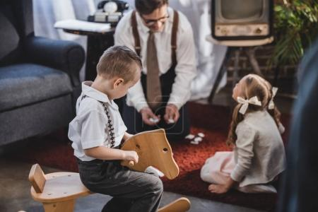 Photo for Little boy sitting on rocking horse while father with daughter playing dominoes behind, 50s style family - Royalty Free Image