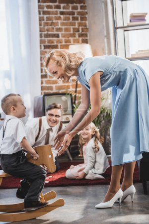 happy mother, father and sister looking at cute little boy sitting on rocking horse at home, 50s style