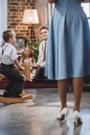 Foto de Sección baja de padre con dos niños mirando a la madre en primer plano, estilo de la década de 1950 - Imagen libre de derechos