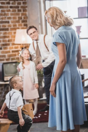 Photo for Happy 1950s man and kids looking at beautiful woman in blue dress at home - Royalty Free Image