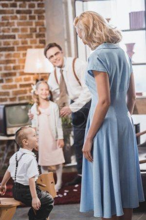 Photo pour Heureux homme des années 1950 et enfants regardant la belle femme en bleu s'habillent à la maison - image libre de droit
