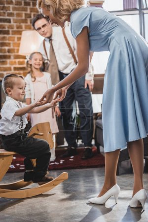 happy 50s style family looking at cute little boy sitting on rocking horse at home