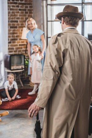 Photo pour Vue arrière du père venant de maison et vous cherchez à l'heureuse famille, années 1950 style - image libre de droit