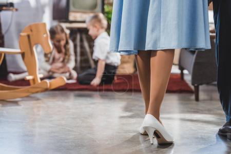 Photo pour Faible section des parents debout ensemble tandis que les petits enfants jouent à la maison, style années 1950 - image libre de droit