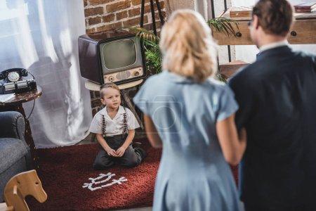 Photo pour Vue arrière du parents rassemblés et regardant mignon petit garçon jouant avec des tuiles de domino, style années 1950 - image libre de droit