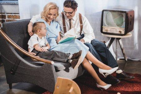 Photo pour Années 1950 heureux style famille assis sur le canapé et la lecture livre ensemble - image libre de droit