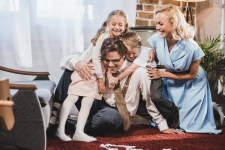 Photo for Cheerful retro styled family hugging while playing dominoes at home - Royalty Free Image