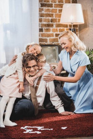 happy vintage family hugging while playing dominoes at home