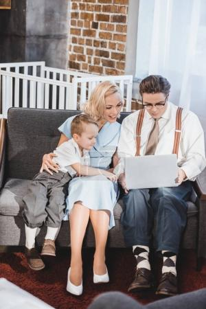 smiling 50s style family using laptop together at home