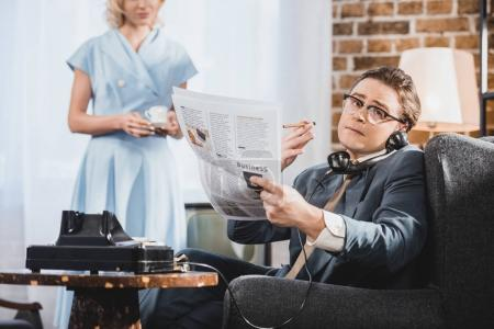 Man in suit smoking cigarette, reading newspaper and talking by vintage telephone while wife holding cup of coffee behind