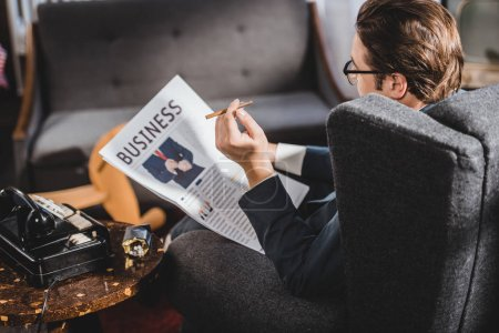 Photo for Man in suit and eyeglasses holding cigarette and reading business newspaper - Royalty Free Image
