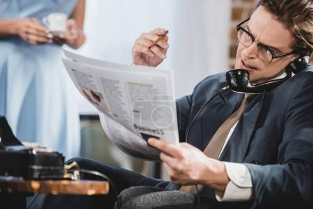 man in suit reading newspaper and talking by vintage telephone
