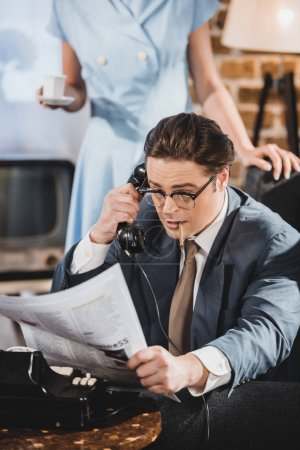 Foto de Hombre con cigarrillo, leer el periódico y hablar por teléfono vintage mientras que la mujer sostiene la taza de café detrás de - Imagen libre de derechos