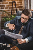 emotional man in suit and eyeglasses pointing at newspaper and talking by vintage telephone