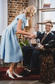 smiling woman pouring coffee to happy husband in suit and eyeglasses sitting in armchair, 1950s style