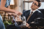 cropped shot of woman pouring coffee to husband in suit reading newspaper, 1950s style