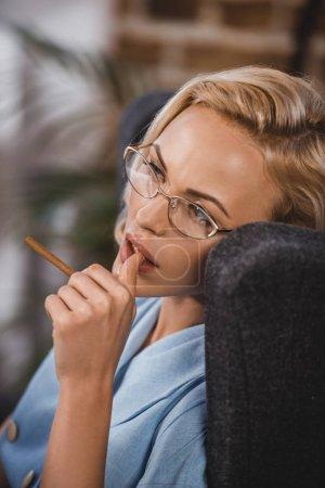 Photo pour Belle femme blonde à lunettes tenant cigarette et de la recherche, la cinquantaine style - image libre de droit