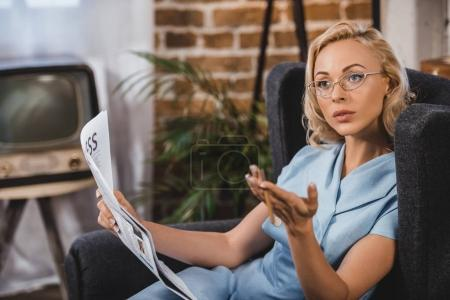 Photo for Beautiful blonde woman in eyeglasses holding newspaper and looking away, 1950s style - Royalty Free Image