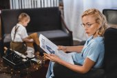 woman in eyeglasses reading business newspaper while little son sitting on rocking horse behind