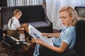 """Постер, картина, фотообои """"женщина в очки, чтение деловая газета время маленький сын, сидя на тряся лошадь позади"""""""