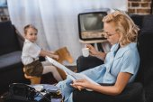woman in eyeglasses holding cup of coffee and reading newspaper while little son sitting on rocking horse behind, 50s style family