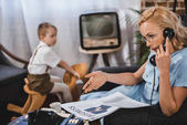 woman in eyeglasses reading business newspaper and talking by vintage telephone while little son sitting on rocking horse behind, 50s style family
