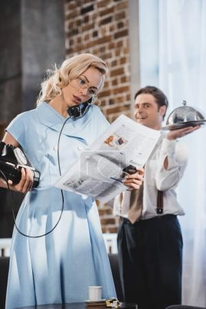 serious woman reading newspaper and talking by vintage telephone while husband holding meal behind, 50s style
