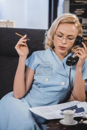 Photo pour Belle femme blonde à lunettes fumer cigarette et parler par téléphone vintage - image libre de droit