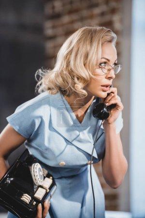 Photo pour Émotionnelle femme blonde à lunettes parler par téléphone vintage et à la recherche de suite - image libre de droit