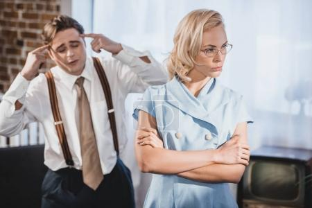 offended woman standing with crossed arms and looking away while emotional husband gesturing with hands behind, 1950s style