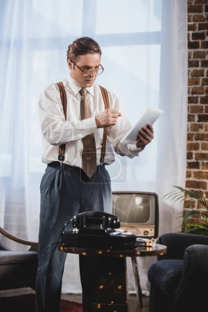retro styled man in eyeglasses using digital tablet at home